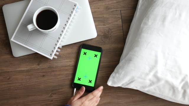 vidéos et rushes de à l'aide de smartphone qui, sur plancher en bois dans la salle de séjour. vue du haut. mode de vie décontracté - modèle réduit