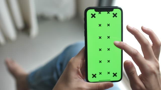 vidéos et rushes de à l'aide de smart phone avec écran vert, chroma key - tenir