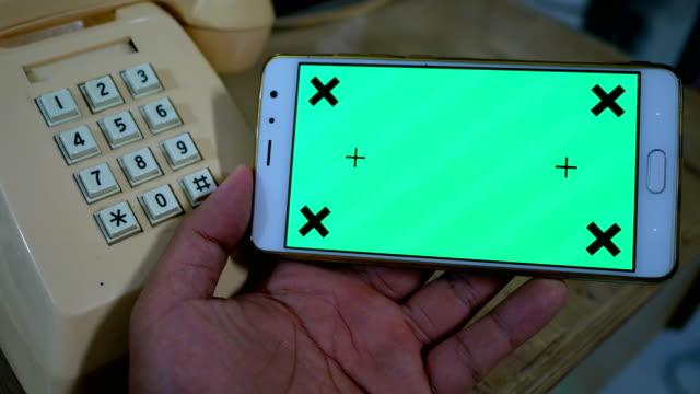 テーブルの上の古いビンテージ電話近くの緑色の画面でスマート フォンを使用してください。 - 受話器点の映像素材/bロール