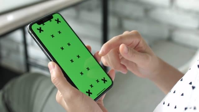 vídeos de stock, filmes e b-roll de usando o telefone inteligente com tela verde - rolando
