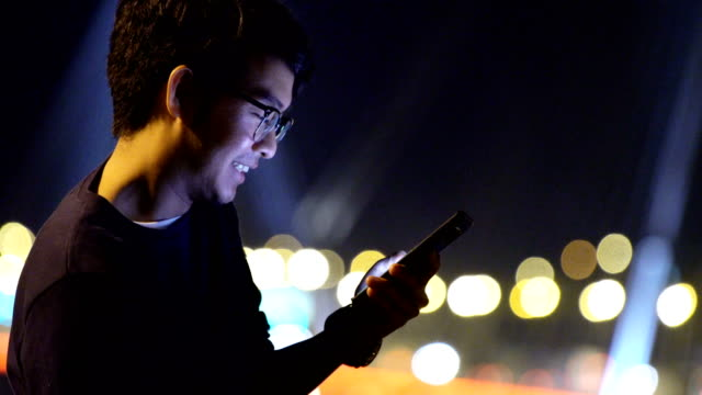 using smartphone at night in the city - mobile app stock videos & royalty-free footage