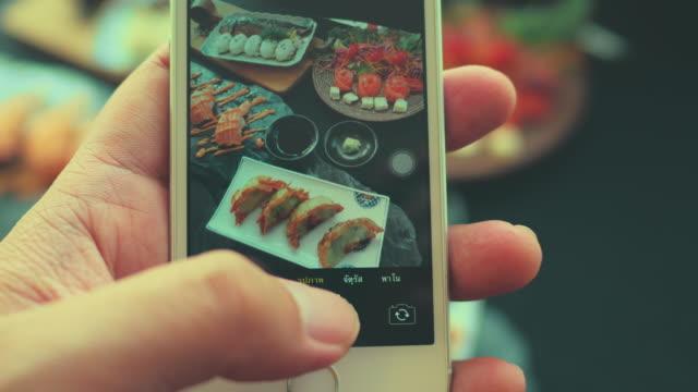 vídeos y material grabado en eventos de stock de uso de teléfono inteligente tomando fotos de la comida japonesa - comida china