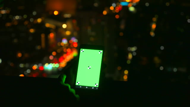 Using Smartphone With Green Screen in Portrait Mode at Rooftop.
