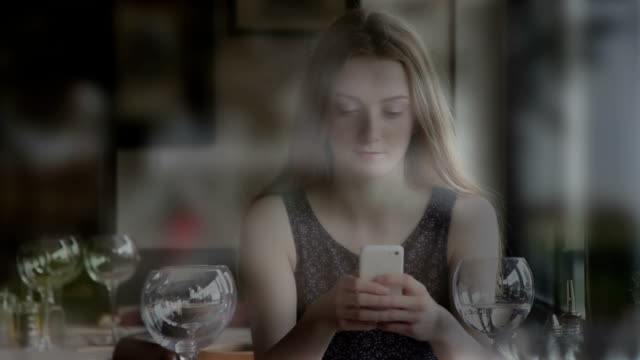 Using smartphone, young woman in a restaurant, view through a window.
