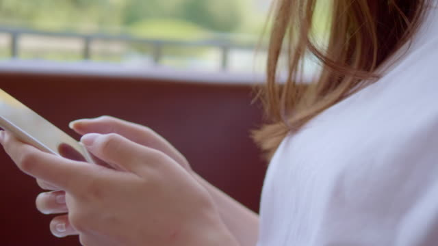 Using smartphone, young woman in cafe