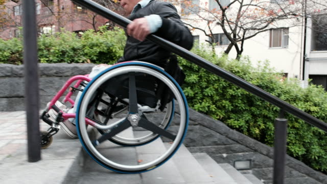 vídeos de stock e filmes b-roll de using stairs in a wheelchair - degraus