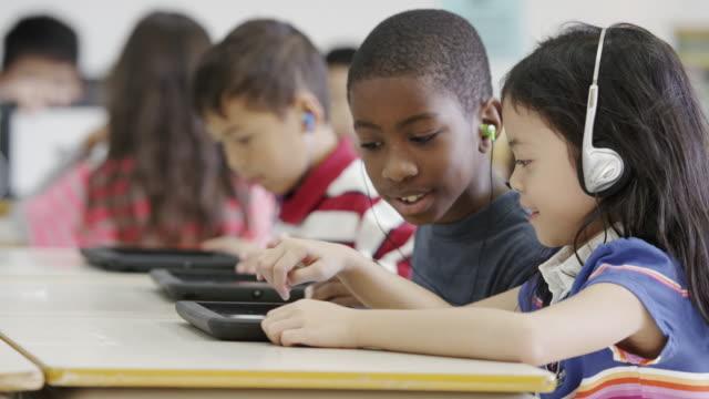 vídeos y material grabado en eventos de stock de usando tableta y tecnología informática en tercer grado de escuela primaria - auriculares aparato de información