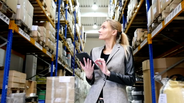 Using tablet and examining the orders in warehouse