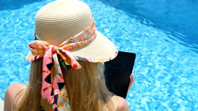Using tablet by the resort pool