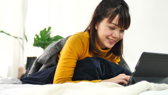 vídeos de stock, filmes e b-roll de usando o tablet pc em casa - reclining