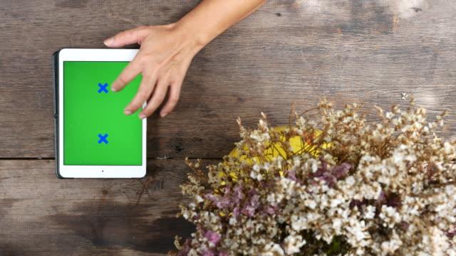 stockvideo's en b-roll-footage met met behulp van tablet pc met cutter bloem op houten tafel, groen scherm concept - table top view
