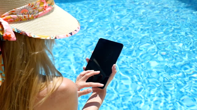 Using tablet & resort swimming pool