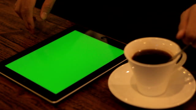 Using Tablet with a Green Screen close up in the cafe