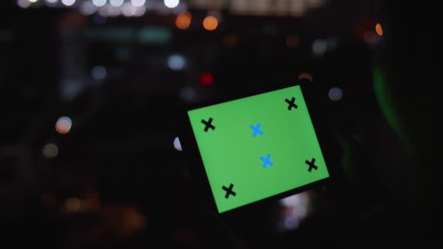 vídeos de stock, filmes e b-roll de usando tablet com tela verde à noite - modelo web