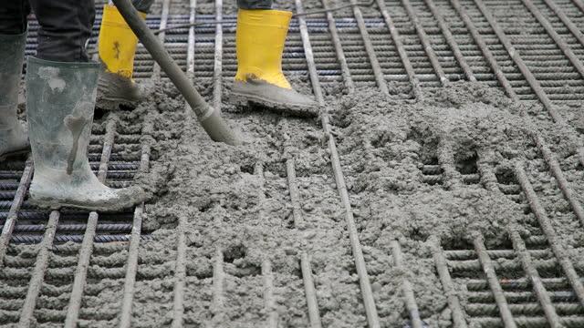 バイブレーターを使用して金属グリッドを通してコンクリートを押す - セメント点の映像素材/bロール