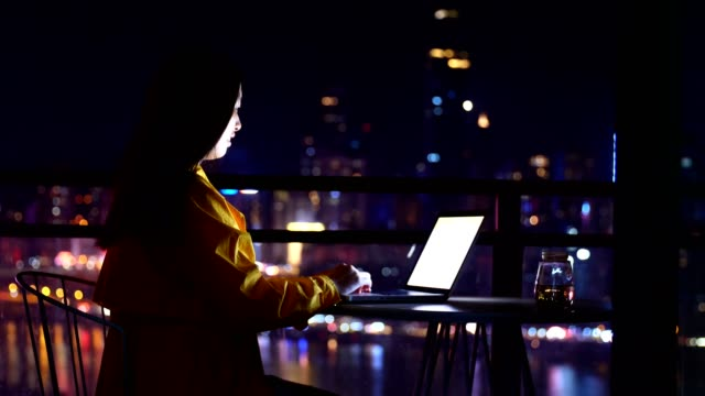 usingwoman using laptop against the urban skyline at night - e learning stock videos & royalty-free footage