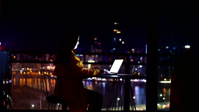 usingWoman using laptop against the urban skyline at night