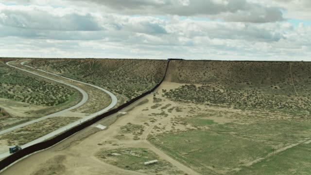 us/mexico border wall crossing desert near el paso - aerial - surrounding wall stock videos & royalty-free footage