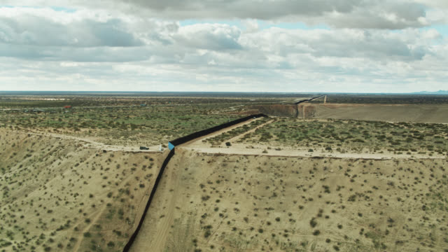 us/mexico border wall near el paso running up steep hillside - aerial - surrounding wall stock videos & royalty-free footage