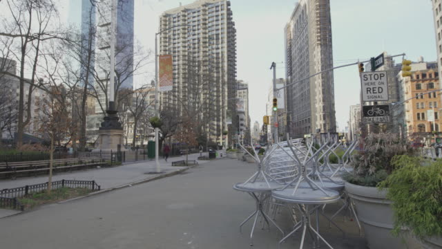 usually crowded flatiron public plaza, at the corner of 5th avenue and east 23rd street, now deserted because of covid-19 coronavirus outbreak. new yrk city, usa - economy stock videos & royalty-free footage