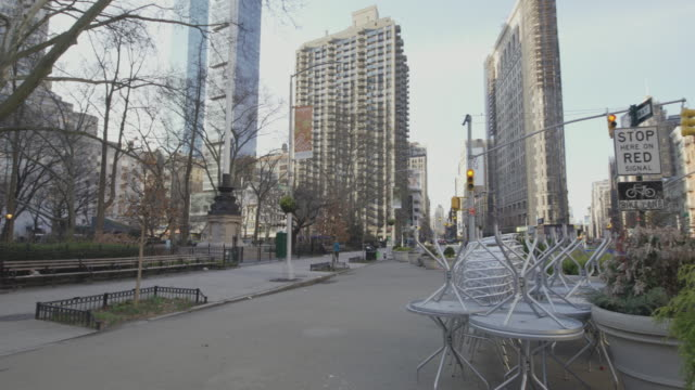 usually crowded flatiron public plaza, at the corner of 5th avenue and east 23rd street, now deserted because of covid-19 coronavirus outbreak. new yrk city, usa - lockdown stock videos & royalty-free footage