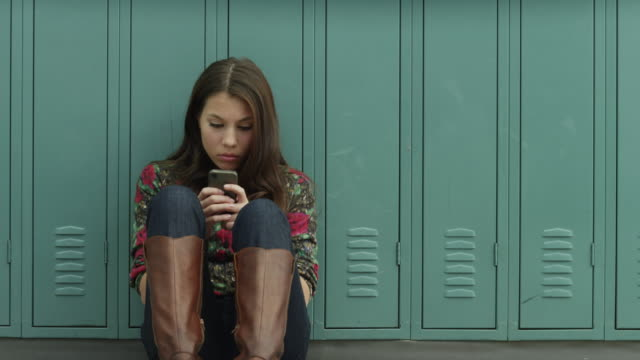 usa, utah, alpine, teenage girl (14-15) sitting at school and using mobile phone - 半狂乱点の映像素材/bロール