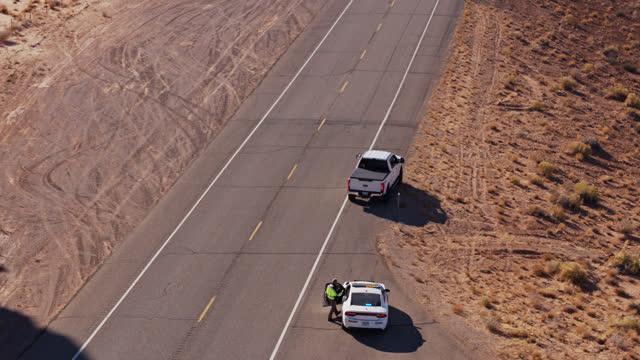 utah highway patrol returning to car - aerial - ökenklimat bildbanksvideor och videomaterial från bakom kulisserna