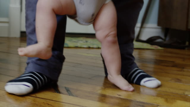 USA, Utah, Orem, Father assisting son (6-11 months) with first steps