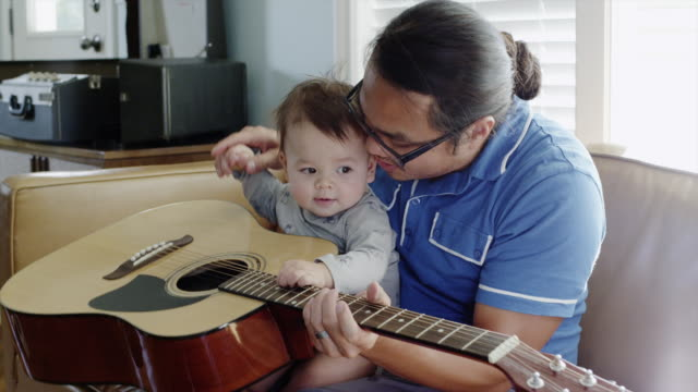usa, utah, orem, father with son (6-11 months) playing guitar - 6 11 months stock-videos und b-roll-filmmaterial