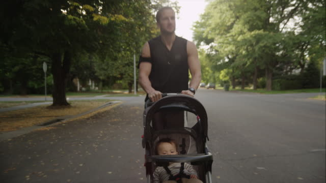 USA, Utah, Provo, Smiling father jogging with son (6-11 months) in stroller