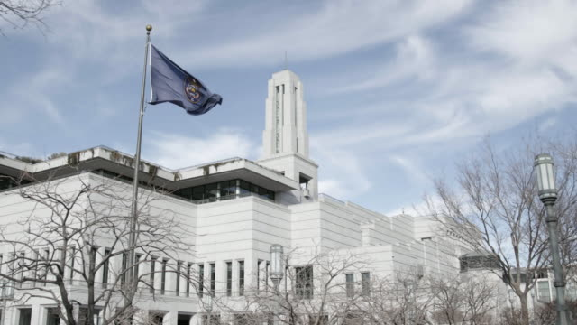 Utah state flag in front of the LDS Convention Center, slow motion