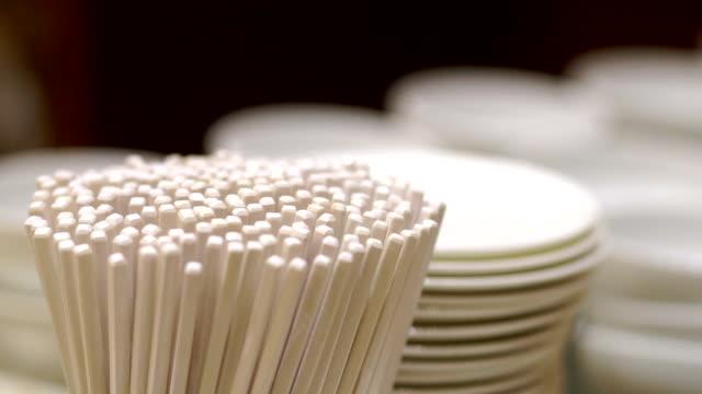 vidéos et rushes de stockage d'ustensile avec plusieurs baguettes, blanc bols et assiettes. - bol vide