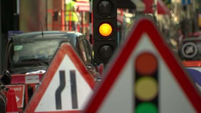 utility companies could be charged by the hour for roadworks england ext close shot of roadworks sign and traffic cone temporary traffic lights... - itv weekend late news点の映像素材/bロール