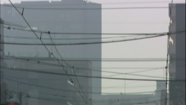 utility lines and electric cables crisscross above a busy street in airpolluted kumamoto - crisscross stock videos & royalty-free footage