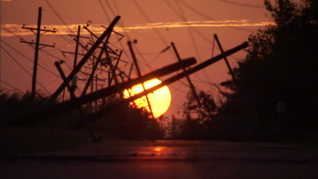 utility transmission poles tilt across a river in a hurricane's aftermath. - extreme weather stock videos & royalty-free footage