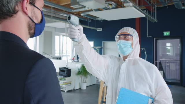 vídeos de stock, filmes e b-roll de funcionário de serviços públicos verificando sintomas covid-19 de funcionário no escritório - part of a series