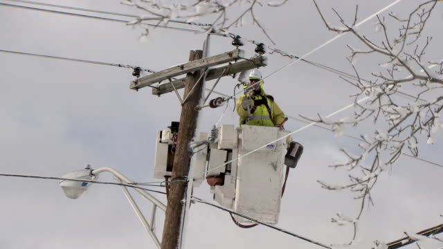utility worker in cherry picker working on powerlines after snowstorm - medium - electrician stock videos and b-roll footage