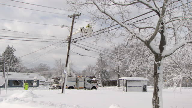 utility worker in cherry picker working on powerlines after snowstorm - wide - cherry picker stock videos & royalty-free footage