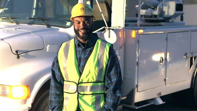 utility worker in safety vest, by truck - addetto alla manutenzione video stock e b–roll