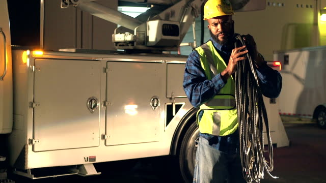 utility worker in safety vest lifting cables, by truck - heavy goods vehicle stock videos & royalty-free footage