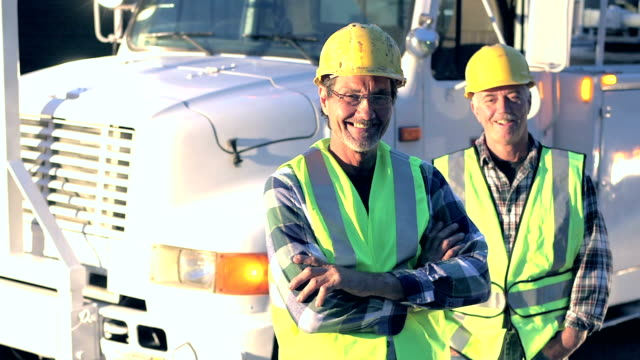 utility workers in safety vests and hardhats by truck - addetto alla manutenzione video stock e b–roll