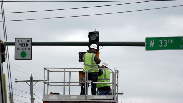 utility workers repair traffic light - addetto alla manutenzione video stock e b–roll