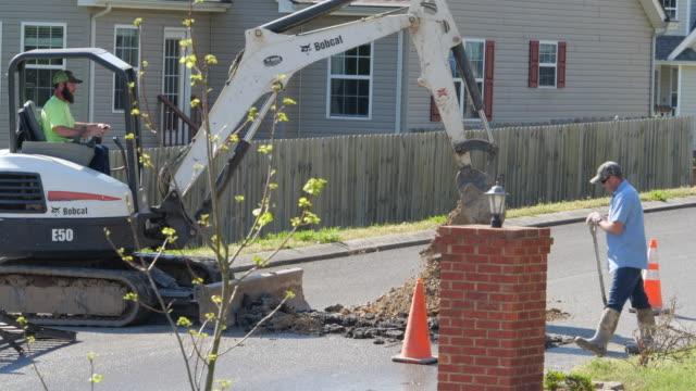 utility workers repairing road on underground water leaking issue in a neighborhood in georgia, usa - leaking stock videos & royalty-free footage