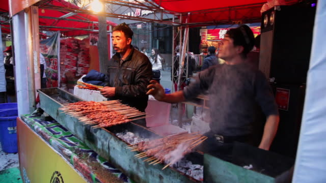 MS Uygur young people are barbecuing kebabs in market / xi'an, shaanxi, china