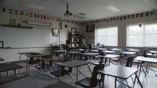 a vacant classroom sits filled with empty school desks. - back to school stock videos & royalty-free footage