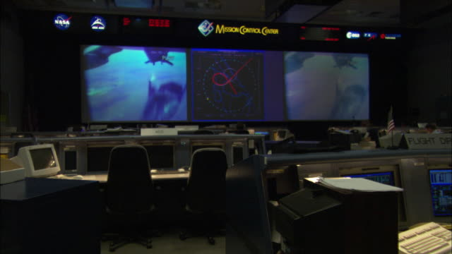 ws vacant desks with computer screens in mission control room, video of  test drop of x-38 vehicle on main screens, houston, texas, usa - control stock videos & royalty-free footage
