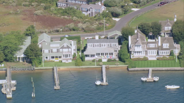 AERIAL Vacation cottages at water's edge with private piers, docks, and jetties / Nantucket, Massachusetts, United States