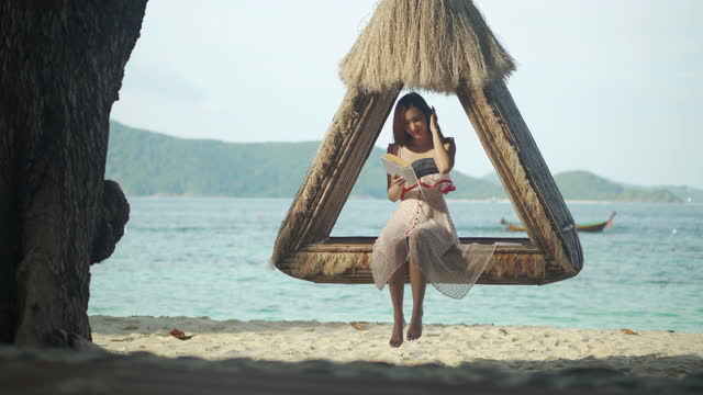 vacation of asian young female age 27 yearold reading on book while sitting  hammock at resort in phuket thailand.she's enjoying sunny day on the beach.phuket, thailand concept. - wonderlust stock videos & royalty-free footage