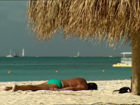 a vacationer sunbathes under a thatched cabana - strohdach stock-videos und b-roll-filmmaterial