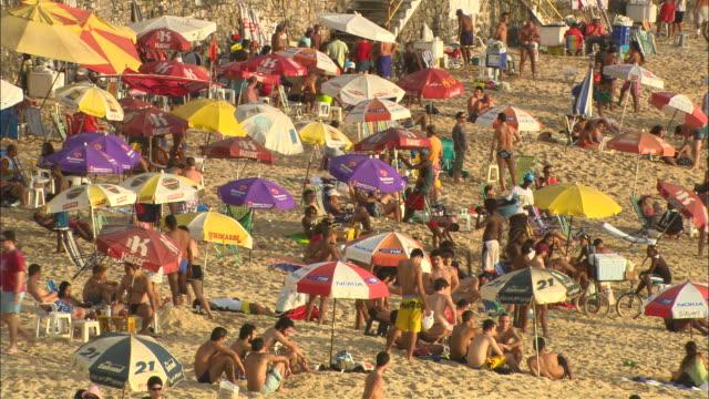 vacationers cluster around beach umbrellas at ondina beach. - bahia state stock videos & royalty-free footage